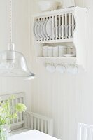 Plate rack with cup hooks and pendant lamp with glass lampshade above dining set in white, Scandinavian kitchen