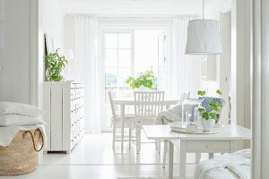 Open-plan, white, shabby-chic interior with green houseplants