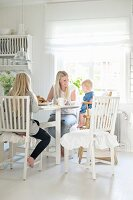 Mother, daughter and baby in high chair at dining table in white, country-house kitchen