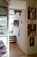 Gallery of pictures on pale green wall with view into bedroom