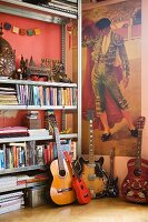 Corner of eclectic room with torero poster, shrine on shelf, books and various guitars