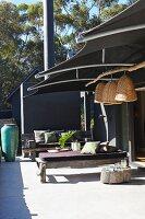 Rustikale Holzbänke mit Liegepolster auf moderner Terrasse, darüber Sonnenschutz aus dunklem Stoff und aufgehängte Stroh Lampenschirme