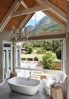 Freistehende Badewanne und Polstersessel auf Galerie, vor offener Faltschiebetür und Blick in sonnigen Garten