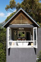Modernes Wohnhaus mit grauer Fassade, offene Faltschiebetüren und Blick ins Bad