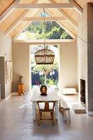 Essplatz mit rustikalem Flair und Hängeleuchte mit Korbschirm unter sichtbarem Dachstuhl mit Bambusabdeckung