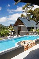 Zeitgenössischer Pool mit integriertem Grillplatz aus Natursteinen, vor Wohnhaus in tropischem Umfeld