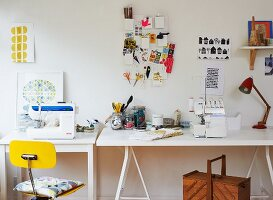 Improvised desk on trestles below mood board with office utensils on wall
