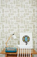 Retro table lamp and typewriter on wooden table against patterned wallpaper