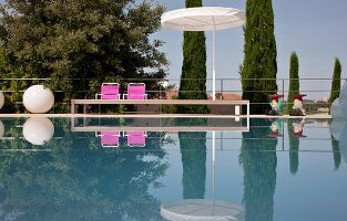Elegant pool, parasol, pink chairs and spherical floor lamp