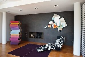 Chaise with black and white, leaf-patterned upholstery and colourful, designer chest of drawers in front of dark grey, tiled wall with set of mirrors and integrated fireplace