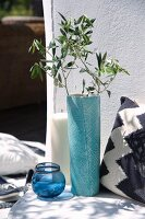 Olive branch in turquoise vase, glass tealight holders, large pillar candle and cushion