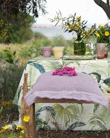 Purple linen cushion on rustic wooden bench next to set garden table