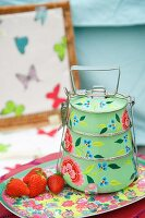 Vintage-style dinner pail with floral pattern and fresh strawberries on tray