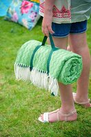 Rolled, green picnic blanket held by girl in garden