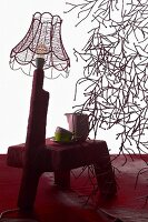 Footstool wrapped in red cover with wire lampshade on integrated lamp base next to bush-like tangle of fairy lights