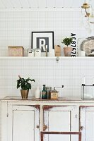 White, shabby-chic dresser and kitchen shelf on grey and white checked wall