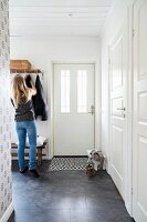 Woman in front of coat rack in rustic, white foyer with dark grey tiled floor and door mat with geometric pattern