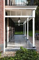 Veranda with white wooden structure and grey stone floor adjoining brick house