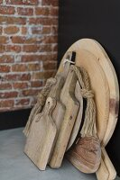 Wooden chopping boards in front of brick wall