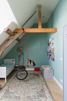 Stylised rocking horse made from tyre hung from roof beam in child's bedroom