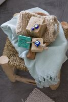 Bars of soaps on cords with beads, loofah glove and towel on rush-bottom stool