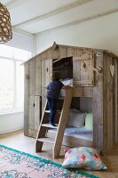 Two children's cubby beds in rustic wooden house with child climbing ladder; Oriental rug and large cushion on floor