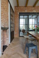 Brick wall in dining room; glass and steel sliding element in doorway leading to living room