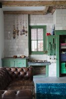 Vintage, green-painted wooden fittings against tiled wall with decorations hanging from hooks; old, leather sofa in foreground