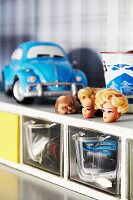 Barbie-doll heads on top of old cabinet with glass storage containers