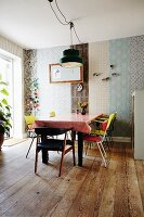 Dining area with colourful, retro chairs around table, wall decorated with strips of various wallpapers and rustic wooden floor