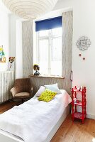 Simple bed below window, red shelving unit used as bedside table and armchair in corner