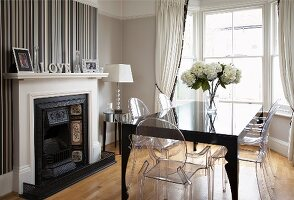 Elegant dining room with bay window, Ghost chairs at black, postmodern table and open fireplace