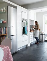 Woman in contemporary kitchen with white, fitted cupboards and integrated fridge