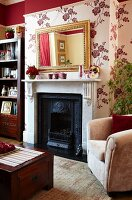 Wall decorated with dark red section above picture rail and floral wallpaper below in traditional interior; antique mirror above English fireplace