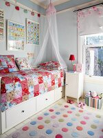 Colourful polka-dot rug next to bed with storage drawers and patchwork blanket in child's bedroom painted pale blue