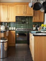 Fitted kitchen with country-house-style, oak fronts and dark green wall tiles