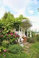 Romantic summer house with climber-covered porch and flowering hydrangea under a blue sky