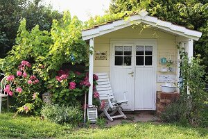 Romantic, climber-covered, wooden summer house painted pastel yellow with armchair under porch