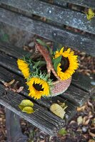 Basket of sunflowers and fallen leaves on weathered wooden bench outdoors
