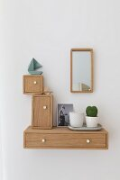 Wooden boxes of various shapes and sizes hung on wall around mirror