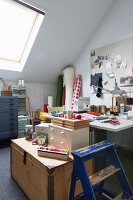Wooden trunk, desk and wooden ladder with peeling paint in attic study