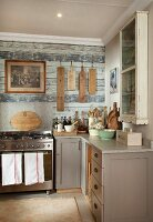 Rustic kitchen - counter with grey-painted base units and modern, stainless steel gas cooker