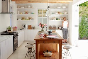 Free-standing, solid-wood island counter in bright, sunny kitchen with woman in background at kitchen counter