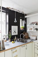 White kitchen counter against black wall with window and creative lamps