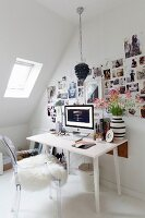 Ghost chair with white sheepskin blanket in front of desk, photos stuck to wall and skylight in sloping ceiling