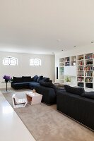 Spacious interior with black sofa combination, child's chair with matching table and ecru rug