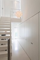 Fitted cupboards and white staircase in narrow foyer