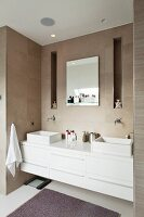 White washstand with twin countertop basins built into niche in tiled wall