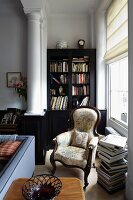 Stacked books next to antique reading chair below window; bookcase in niche next to wall projection with classic supporting column
