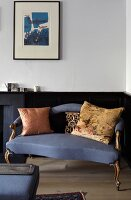 Blue-covered, delicate antique sofa below modern artwork in corner of room with black wainscoting